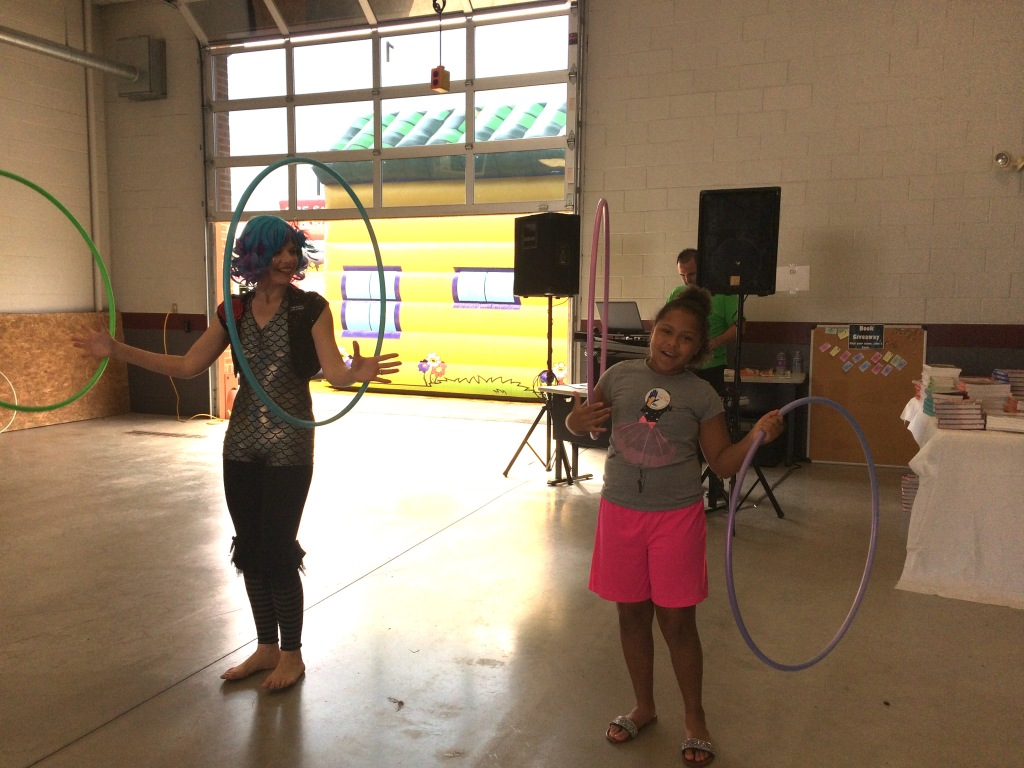 Jenny Hill of Acts of Jennius helps a girl learn to twirl a hoop on each hand.